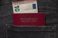 El pasaporte ruso y una cuenta de 10 euros se pegan fuera del bolsillo trasero de vaqueros imágenes de archivo libres de regalías