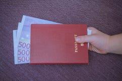 El pasaporte transporta una mano del ` s del niño Foto de archivo