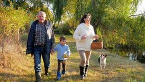 El paseo de la familia, abuelo feliz con el nieto así como perro pasa a través de bosque en la pesca al lago en el fin de semana metrajes