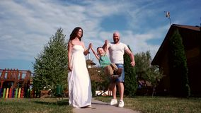 El paseo de la familia, padres está con el niño, la madre y el padre llevando a cabo las manos de su hijo, muchacho que tiene ris almacen de video