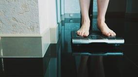 El paseo de la muchacha en piso se levanta en escalas modernas en el apartamento weighing slimness almacen de metraje de vídeo