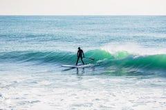 El paseo de la persona que practica surf encendido se levanta el tablero de paleta en onda del azul de océano Fotos de archivo libres de regalías