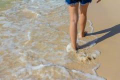 El paseo de la señora de pierna en la playa y la ola oceánica la estrellan Foto de archivo libre de regalías