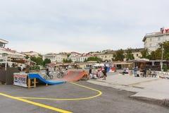 El paseo de la tarde del verano de las adolescencias anda en monopatín y monta en bicicleta en las calles de la ciudad Fotografía de archivo