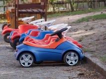 El paseo de los niños en los coches plásticos Imagen de archivo libre de regalías