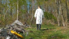El paseo del hombre a través de la madera cerca del midden almacen de metraje de vídeo