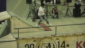 El paseo del patinador del rodillo en la cerca, salta de él, pie del gancho agarrador Manía extrema Competencia en skatepark almacen de metraje de vídeo