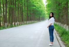 El paseo libre de la mujer de los carelss en el camino en el bosque al aire libre goza del aire fresco Foto de archivo
