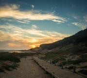 El paseo marítimo lleva a la playa debajo del sol poniente imágenes de archivo libres de regalías