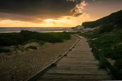 El paseo marítimo lleva a la playa y al sol poniente imágenes de archivo libres de regalías