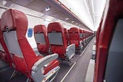 El pasillo largo con filas de se sienta en economía del aeroplano Imagen de archivo libre de regalías