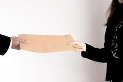 El paso del hombre de negocios la carpeta a la mujer de negocios en el fondo blanco Foto de archivo