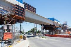 El paso a nivel del camino del centro que era substituido por el skyrail elevó vías del tren en Clayton South, Melbourne Fotografía de archivo