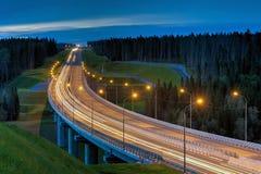 El paso superior y la luz se arrastra en la noche en bosque iluminado de la carretera Imágenes de archivo libres de regalías