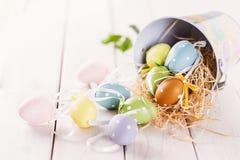 El pastel coloreó los huevos de Pascua sobre el fondo de madera blanco Foto de archivo libre de regalías