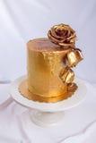 El pastel de bodas adornó el oro, pendiente verde con las flores dibujadas mano Imagenes de archivo