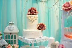 El pastel de bodas blanco adornó el modelo del azúcar en la tabla Fotografía de archivo libre de regalías