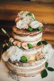 El pastel de bodas con las rosas azotó la crema foto de archivo