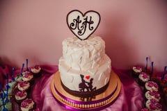 El pastel de bodas con las siluetas de los recienes casados se coloca en tableclot rosado fotos de archivo