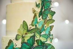 El pastel de bodas de dos niveles se adorna con las mariposas verdes Imagen de archivo