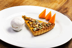 El pastel de calabaza con crema y la calabaza azotadas junta las piezas en la placa blanca Imagenes de archivo