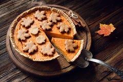 El pastel de calabaza hecho en casa con la rebanada cortó en el fondo de madera para la tabla de cena de la acción de gracias Fotografía de archivo libre de regalías