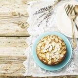 El pastel de pacanas hecho en casa simple adornó con los pétalos de la almendra un fondo de madera que servía el azul usado Pascu Foto de archivo libre de regalías