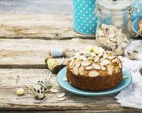 El pastel de pacanas hecho en casa simple adornó con los pétalos de la almendra un fondo de madera que servía el azul usado Pascu Foto de archivo