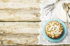 El pastel de pacanas hecho en casa simple adornó con los pétalos de la almendra un fondo de madera que servía el azul usado Pascu Imagen de archivo libre de regalías