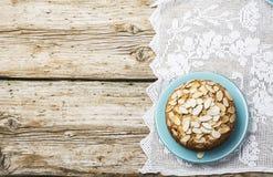 El pastel de pacanas hecho en casa simple adornado con los pétalos de la almendra con un fondo de madera que servía Pascua utiliz Foto de archivo