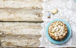El pastel de pacanas hecho en casa simple adornado con los pétalos de la almendra con un fondo de madera que servía Pascua utiliz Imagen de archivo