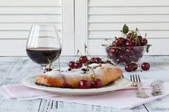 El pastel de queso de la cereza sirvió en una placa del caramelo con el vino rojo Fotos de archivo libres de regalías