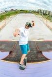 El patinador adolescente cuelga para arriba sobre una rampa en un monopatín en un parque del patín Fotografía de archivo libre de regalías