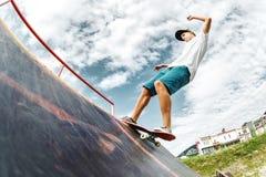 El patinador adolescente cuelga para arriba sobre una rampa en un monopatín en un parque del patín Foto de archivo libre de regalías