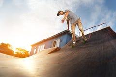 El patinador adolescente cuelga para arriba sobre una rampa en un monopatín en un parque del patín Fotos de archivo