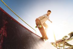 El patinador adolescente cuelga para arriba sobre una rampa en un monopatín en un parque del patín Foto de archivo