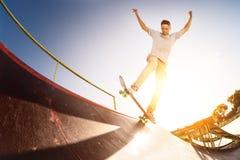El patinador adolescente cuelga para arriba sobre una rampa en un monopatín en un parque del patín Fotos de archivo libres de regalías