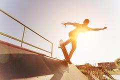 El patinador adolescente cuelga para arriba sobre una rampa en un monopatín en un parque del patín Fotografía de archivo