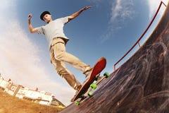 El patinador adolescente cuelga para arriba sobre una rampa en un monopatín en un parque del patín Imagenes de archivo