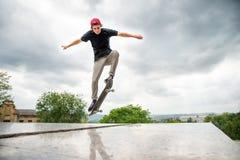 El patinador-adolescente de pelo largo en una camiseta y un sombrero de la zapatilla de deporte salta un callejón contra un cielo Imagen de archivo libre de regalías