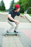 El patinador-adolescente de pelo largo en una camiseta y un sombrero de la zapatilla de deporte salta un callejón contra un cielo Imágenes de archivo libres de regalías