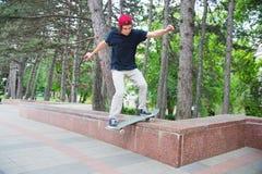 El patinador-adolescente de pelo largo en una camiseta y un sombrero de la zapatilla de deporte salta un callejón contra un cielo Foto de archivo libre de regalías