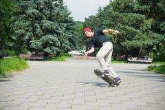 El patinador-adolescente de pelo largo en una camiseta y un sombrero de la zapatilla de deporte salta un callejón contra un cielo Fotos de archivo