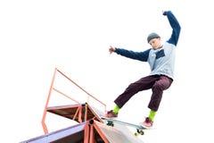 El patinador adolescente en un suéter con capucha y vaqueros resbala sobre una rampa en un monopatín aislado en blanco Fotografía de archivo libre de regalías