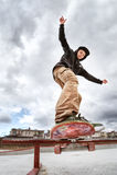 El patinador adolescente en un suéter con capucha y vaqueros resbala sobre una verja en un monopatín en un parque del patín Fotos de archivo