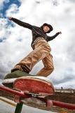 El patinador adolescente en un suéter con capucha y vaqueros resbala sobre una verja en un monopatín en un parque del patín Fotografía de archivo