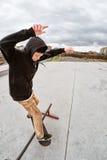 El patinador adolescente en un suéter con capucha y vaqueros resbala sobre una verja en un monopatín en un parque del patín Imagen de archivo