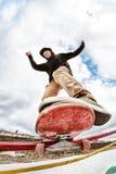 El patinador adolescente en un suéter con capucha y vaqueros resbala sobre una verja en un monopatín en un parque del patín Fotos de archivo libres de regalías