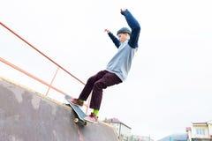 El patinador adolescente en un suéter con capucha y vaqueros resbala sobre una verja en un monopatín en un parque del patín Foto de archivo libre de regalías
