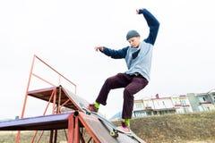 El patinador adolescente en un suéter con capucha y vaqueros resbala sobre una verja en un monopatín en un parque del patín Foto de archivo